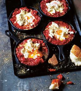 Vier Portionen marokkanische Eier, frisch aus dem Ofen und mit Fladenbrot serviert.