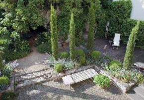 """Blick in den mediterran anmutenden Hofgarten mit erhöhter Holzterrasse; im Hintergrund die alten Kellergewölbe, über denen sich der """"Geheime Garten"""" befindet."""