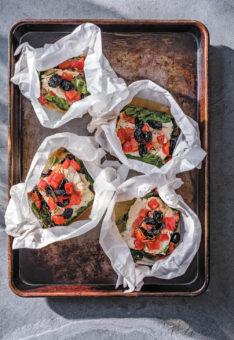 Blechkochbuch Kabeljau in Papierhülle mit Tomaten, Oliven und Spinat