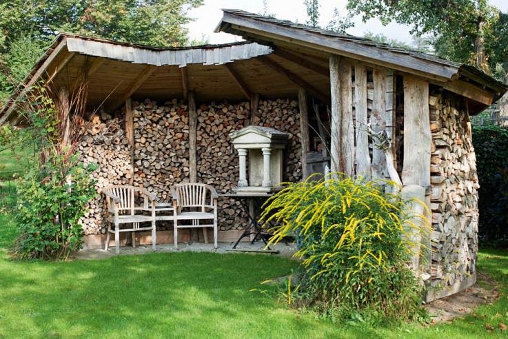 Gartenlaube aus aufgeschichteten Brennholzscheiten