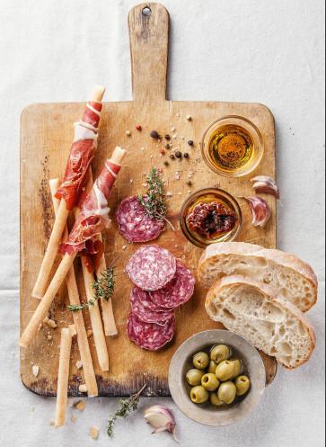 Antipasti: Grissini mit Schinken, Salami, Oliven und Brot auf Holzbrett